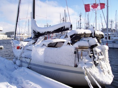 A sailboat tied up to the dock, covered in snow, a Canadian flag flying at the stern.