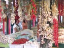 Colourful strings of garlic and chillies in an open market stall.
