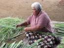 Mary stripping the sharp edges off the Panadanas leaves ready for processing for mat weaving.