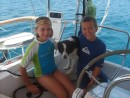 Sierra and John play with Daisy while sailing