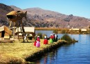 Islas Flotantes on Lake Titicaca. Good view of the reed islands, houses and watchtower. Local Uros women await a boat of tourists.