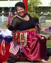 A smiling Tongan lady in the parade with US flags