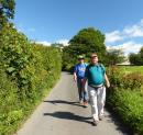 Randall and Mike stride along a narrow Lakeland road