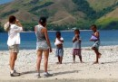 Beth & Linds chat with kids on the beach.  Their shirts are full of mangoes!