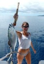 Linds proudly holds up the big pacific bonito she reeled in on the hand line.