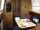 "This view of the saloon (pronounced ""sal ON"") shows the dinng table, convertable to a guest berth, and the entertainment center, so called because it was always entertaining trying to get the TV to work. The steps behind the table lead up to a small rear deck where we stood to operate the boat."
