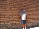 Ian in front of adobe brick wall.
