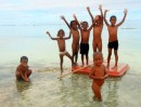 Maunaira kids on some sort of floaty toy -clothing optional for this day at the beach!