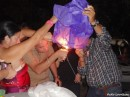 Party guests lighting one of many Chinese lanterns that were sent aloft