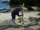 Back on the beach, Sikki began cutting the firewood to size with his machete.