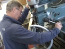 Ted operates a massive machine press to notch the Rocna.