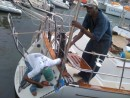 "Ronell and Alan  position the new wind generator pole for installation on the transom. Properly aligning the angled base and keeping the pole on a vertical axis in all directions while the boat bobbed about was challenging. Untimately you eyeball it and say ""go for it""."