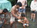 showing how to get coconut meat in a mature coconut. He sits on the tool and scrapes the coconut and the child catches the scrapings. Very effective.