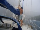 Tidying up the sail in a squall at anchor between the Pitons
