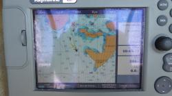 "Chartplotter screen. : .   (Sorry about the reflections off the screen) It's quite old by current standards but does the job for us…….. That's us centre screen, Green line is our heading, Yellow line is apparent wind direction. 5 other vessels nearby from the AIS (There were 97 AIS equipped vessels in range at that time!) Our speed 6.6Kt, A ""Go To"" point set 0.5 Nm away at 3540  - Usually used when aiming for a point many miles away.  The yellow bits and little black crosses are non-boat compatible areas."