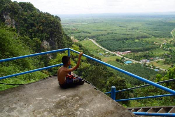 A young boy seemingly contemplates life near the top of the Tiger Cave Temple