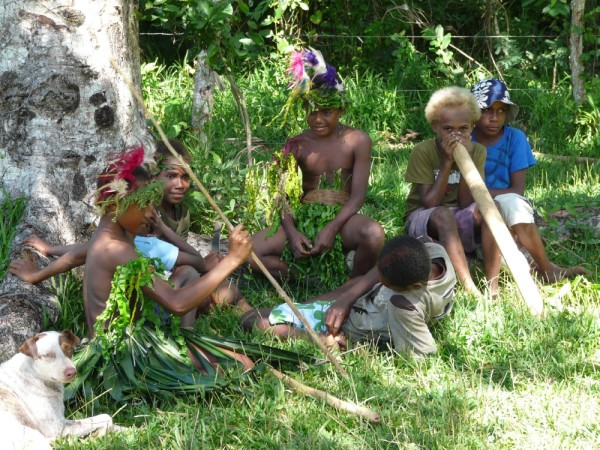 preteens hang out just off the main group.  The blond headed boy holds a bamboo which is used to make a drumming sound