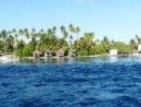 thatched cabins on waters edge near the pass into Fakarava
