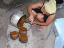 Expertly pouring hot palm sugar into smaller pots