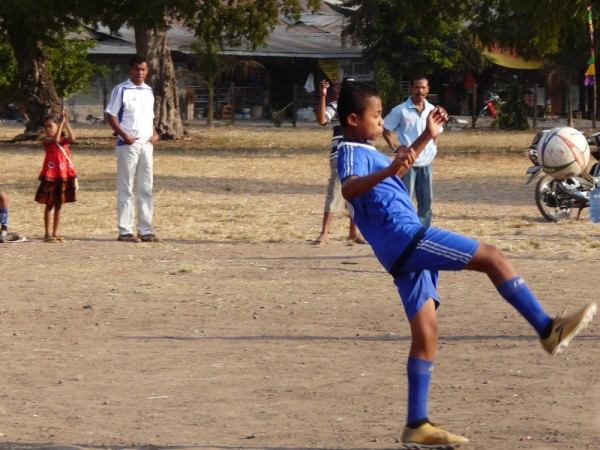 A local soccer game, dirt field, but the soccer boots are cool!