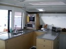 The galley looks out to the back dining area through the sliding glass door and window.