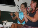 Cammi learning flute from Bobbie Jo while Apple listens; Tahuata, Marquesas