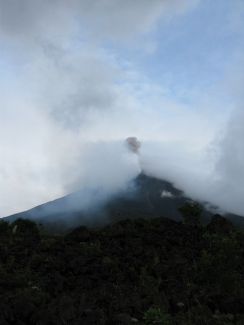 Volcano erupted, dark grey plume visible and rocks spewed