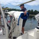Loading the jib.: Peter Backhouse putting the jib in the dinghy, on it