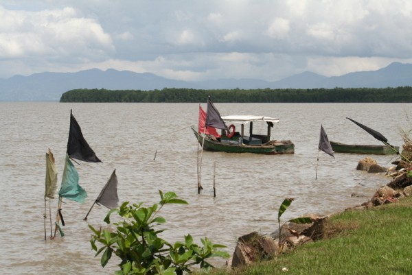 Local fishing boat with prayer flags in foreground