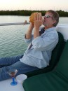 Capn Bill blows conch at sunset