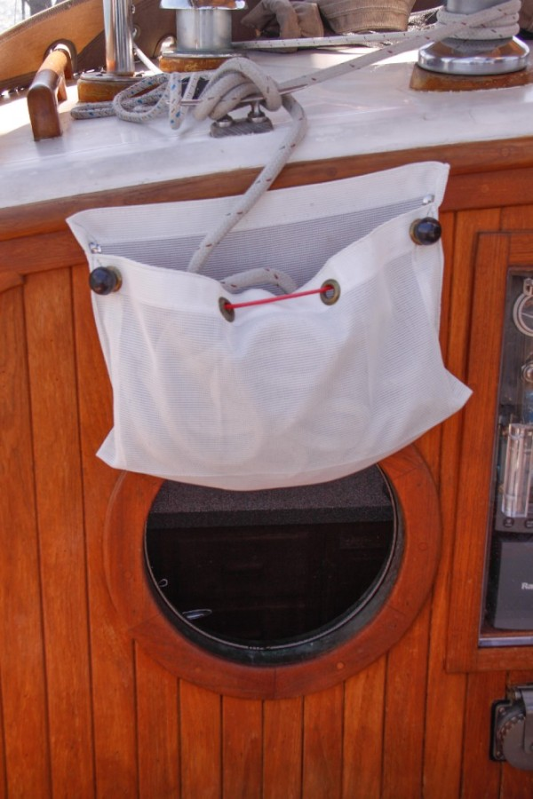 I found some scrap mesh left up by the garbage and turned it into this line bag for the main sheet.  This picture also shows the new bug screen in the galley porthole.