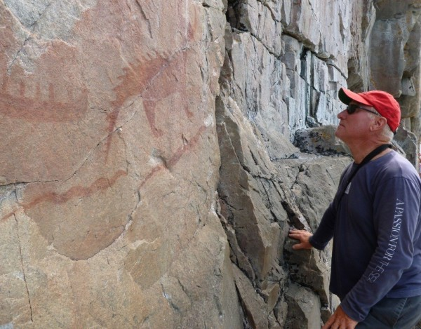On the left a cliff face with a pictograph some hundreds of years old, on the right just an old guy.