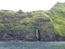 The coast of Fatu Hiva is rugged,  here a tunnel has been eroded through the lava wall.