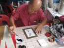 This Chinese gentleman was truly an artist as he plied his trade of calligraphy while making chop pictures.