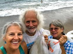 Heidi, Kirk and Judy picking up plastic trash off the beach on World Ocean