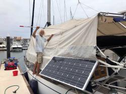 Capitán Kirk cleaning the sun-awning on s/v Due West. The awning also acts as an excellent wind-tunnel, funneling the cooling breezes down through the hatches.