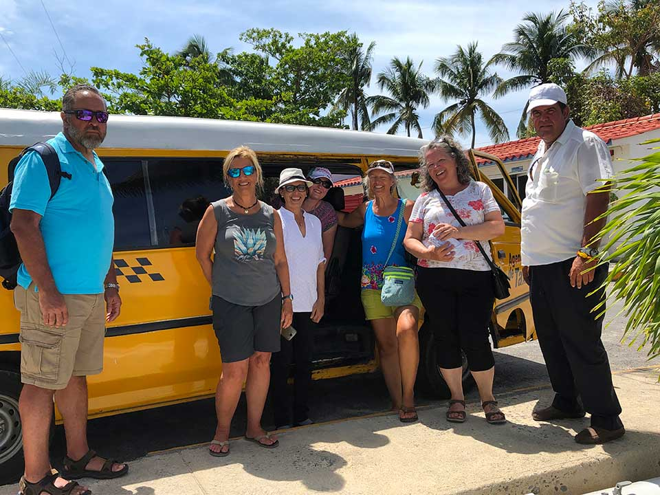 Bel and Gustavo arrived in his taxi-van to pick us up at the Platten Charter Base just as planned. It was so wonderful to see Bel again! We had missed her cheery smile, laugh, and demeanor and were all excited for her to  show us around more of her Caribbean island home. Rob, Val, Bel, Kelly, Heidi, Capitana Teresa, and Gustavo, (photo by Kirk.)