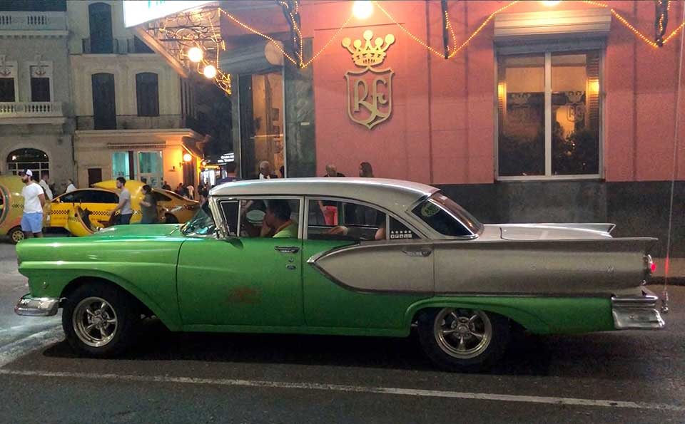 A flashy green and silver 1957 Ford sits in front of the Floridita, Hemingway
