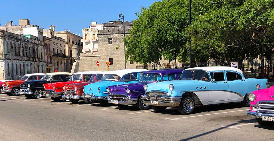 Early morning photo opp with the Classic Cars parked together. Shortly after, they all take off to different parts of the city for Classic Car Taxi Tours.  Cars range from late 1940