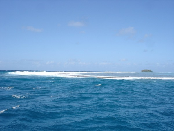 Passe Teavamoa along the east side of Raiatea Island.  This is the south side of the pass.  Waves crashing into the reef.