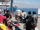 An over loaded motor cycle just coming off the ferry at Samal Island.