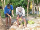 Marc being shown by Sam (the island caretaker) how to crack a green coconut