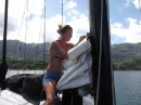 Sitting on top of the main boom, sewing up the mainsail.