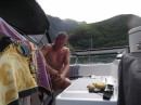 Tom working on opening up a coconut he harvested from a tree.  Anchored in Taioa Bay.