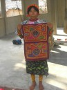 Kuna girl holding up molas Isla Maquina