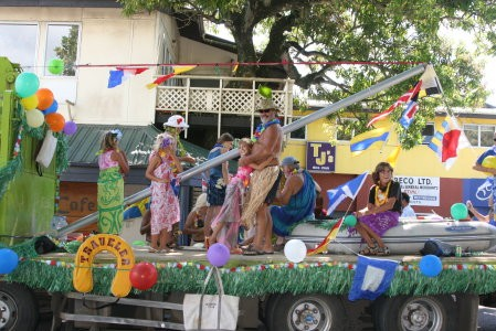 "The ""Yachts of Women of Courage"" float!  Yes!  That is Glen in his grass skirt holding the whisker pole!  He was thankful there wasn"