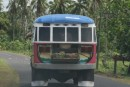 One of the many colorful buses of Samoa!  Notice the woven baskets of coconuts in the back!