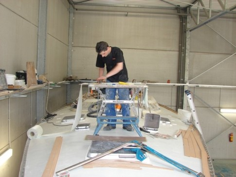 Nearly there - Joeri applying the finishing touches to the new aft locker hatch.